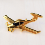 Golden airplane enamel pins